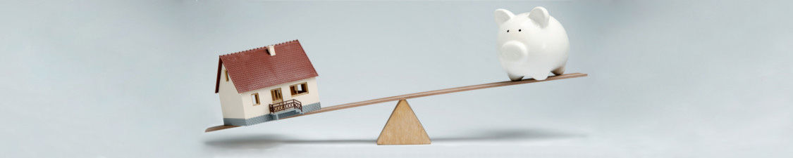 Immobilienschulden Wippe Sparschwein VS. Haus