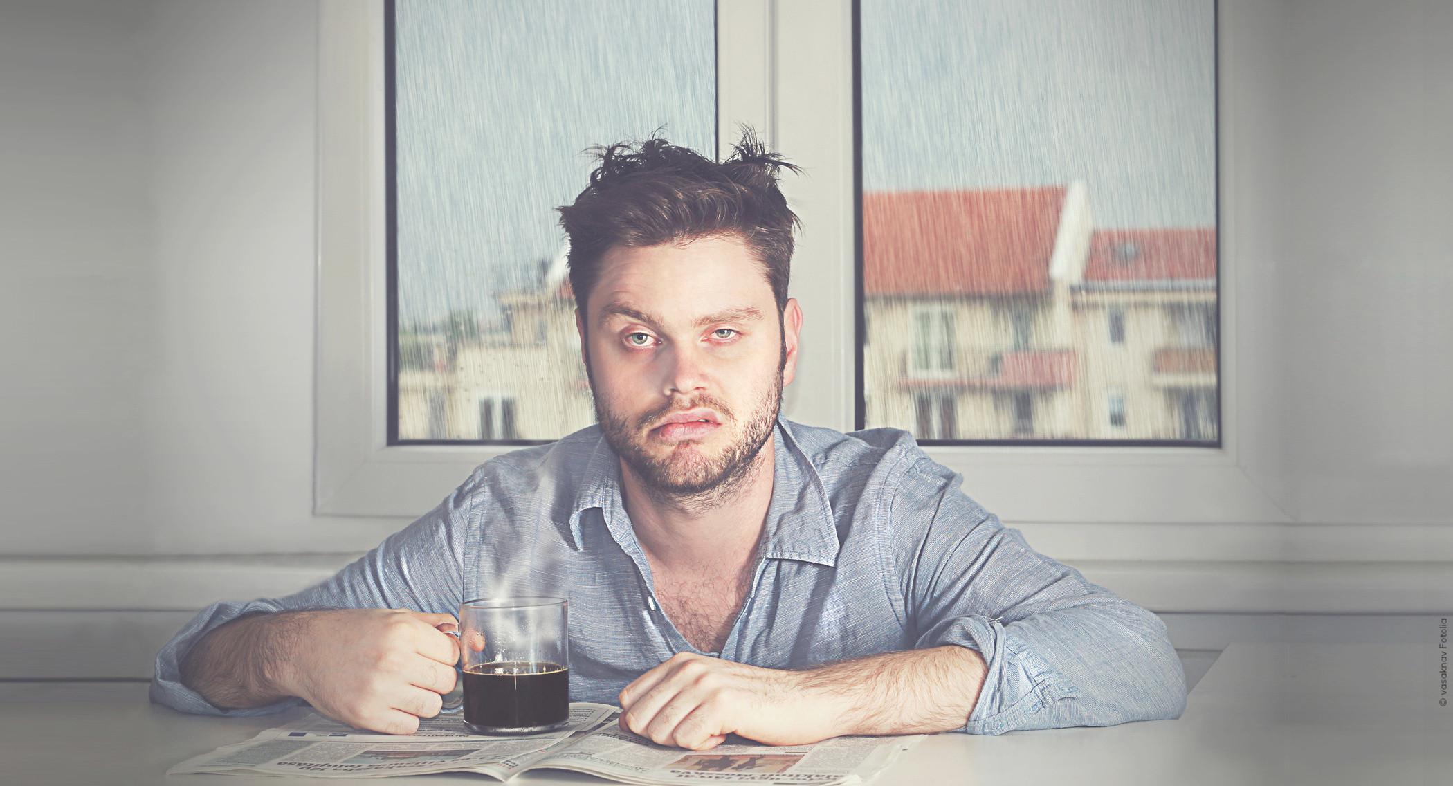 Mann müde und erledigt mit Kaffee